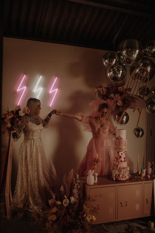 pink dress for wedding with alternative cake table decorated with neon signs and glitter balls
