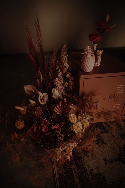Pink floral arrangement with dried grasses, anthuriums  and roses