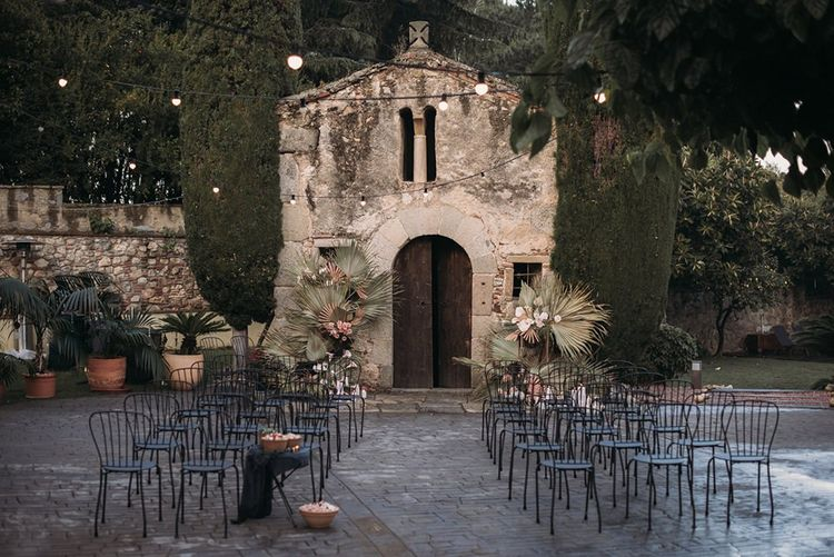 Intimate Outdoor Wedding Ceremony with Festoon Lights and Dried Palm Leaves Decor