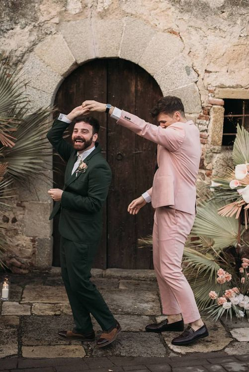 Groom in Pink Wedding Suit Twirling His Partner in a Green Wedding Suit
