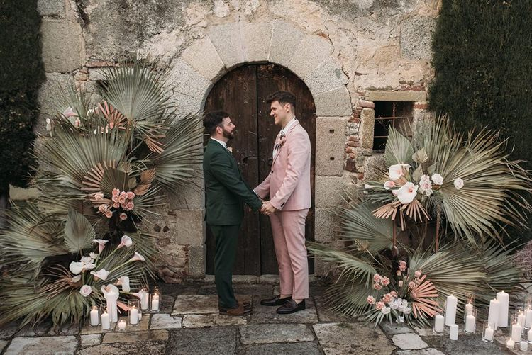 Grooms in Pink and Green Wedding Suits Holding Hands at the Altar Decorated with Palm Leaves, Lilies and Candles