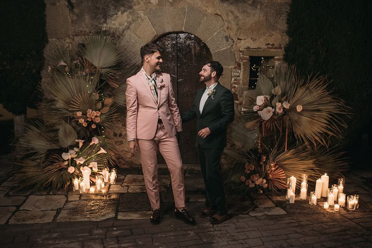 Same Sex Grooms  in Pink and Green Wedding Suits Standing Neck to Candles