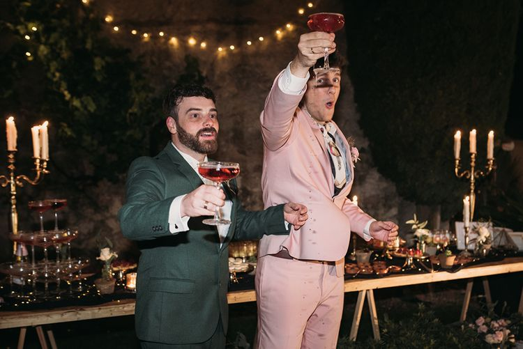 Two Grooms Raising Their Champagne Glasses