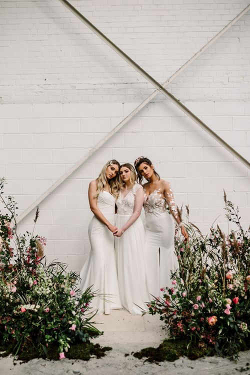 Three Brides Standing by Deep Pink and Foliage Floral Arrangements