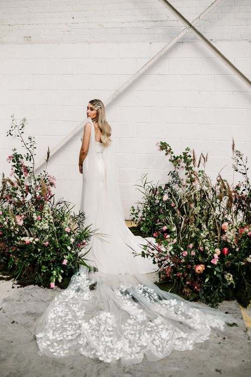 Bride with  Long Lace Wedding  Train Standing by Deep Pink and Foliage Floral Arrangements