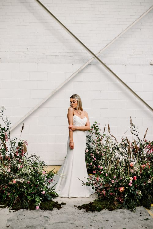 Bride in Fitted Wedding Dress Standing by Deep Pink and Foliage Floral Arrangements