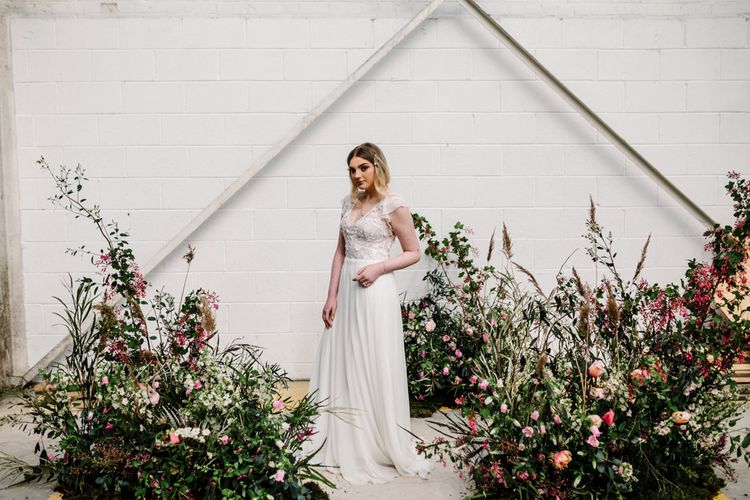 Bride in Lace Bodice and Floaty Skirt Wedding Dress  Standing by Deep Pink and Foliage Floral Arrangements