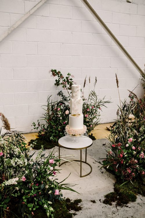 Wedding Cake in Marble Top Nest Table Surrounded by Deep Pink and Foliage Floral Arrangements