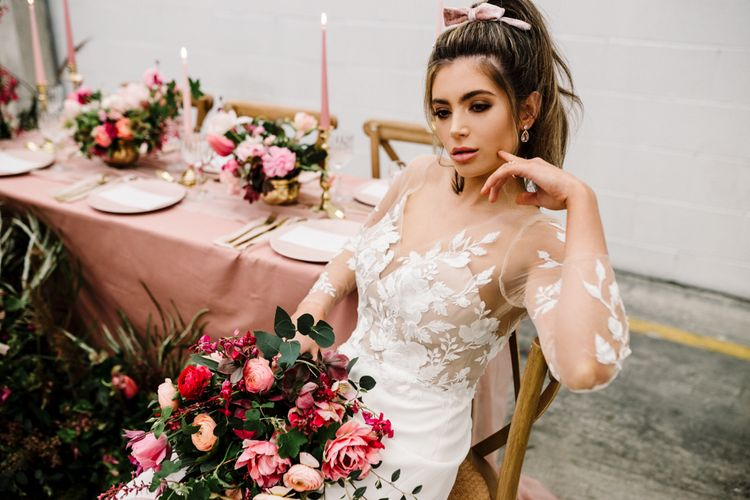 Beautiful Bride with Natural Makeup in a Illusion Lace Wedding Dress Holding a Deep Pink and Green Bouquet