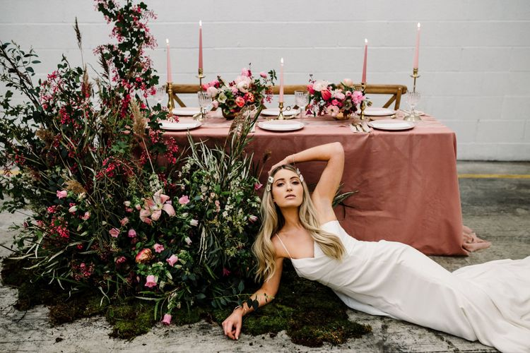 Bride in Fitted Strappy Wedding Dress Next to a Beautiful Light Pink and Dark Pink Tablescape