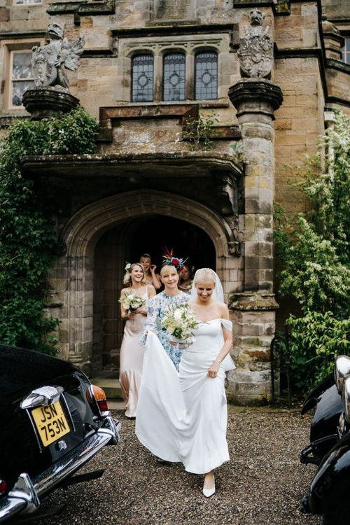 Bride in off the shoulder wedding dress going to the church