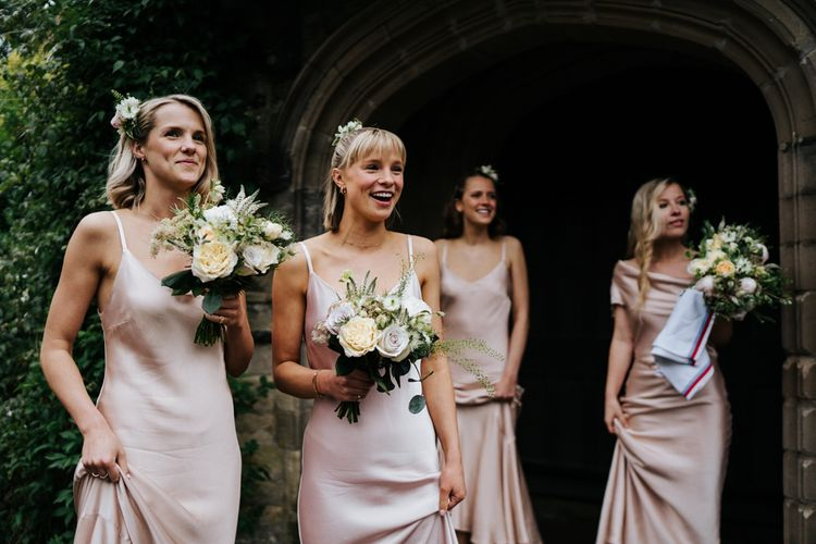 Bridesmaids hold bouquets and smile at bride, off-frame, as she enters her wedding car
