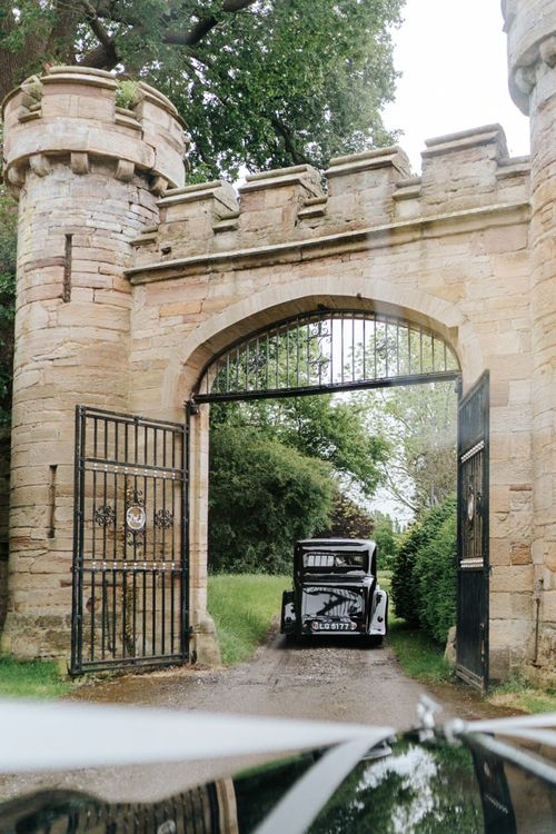 Bride's car passes under fortified gates at Hawarden Castle in Wales, UK