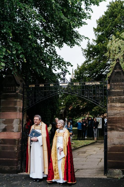 Vicars patiently await arrival of the bride outside of the village church in Hawarden, Wales