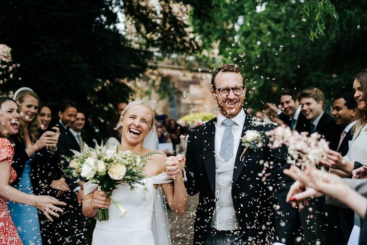 Bride and groom exit the church and walk down the pathway as guests throw confetti at them