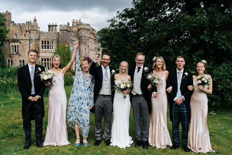 Posed family photograph of bride, groom and bride's family with Hawarden Castle in the background