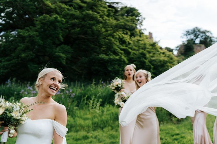 Bride's veil flies out of her hair as bridesmaids look on in amazement