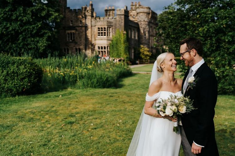 Bride in off the shoulder wedding dress and groom in traditional morning suit standing in front of Hawarden Castle in Wales
