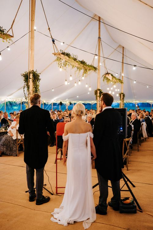 Father of the bride delivering his speech as guests listen attentively inside marquee at Hawarden Castle, Wales