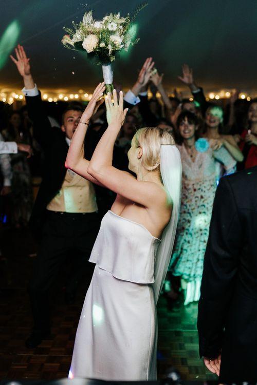 Bride throws bouquet into crowd of keen guests on the dancefloor