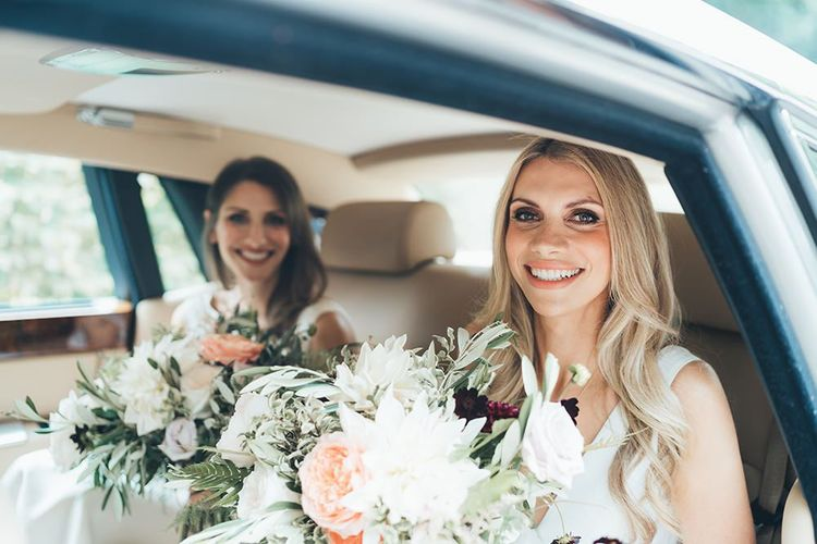 Bride and Bridesmaid in Rolls Royce Wedding Car to Ceremony with Peachy Bouquet