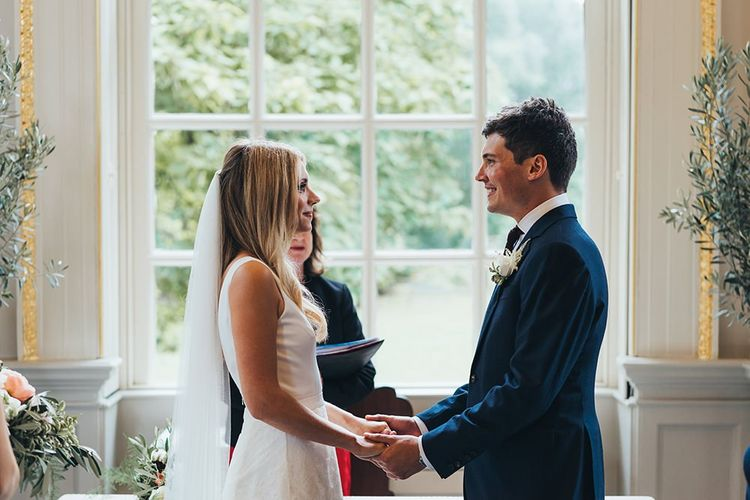 Bride in Charlie Brear Tiered Lace Wedding Dress with Groom in Hackett Suit