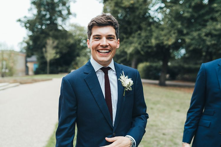 Groom in Navy Suit from Hackett and Burgundy Tie from Gucci with Floral Buttonhole