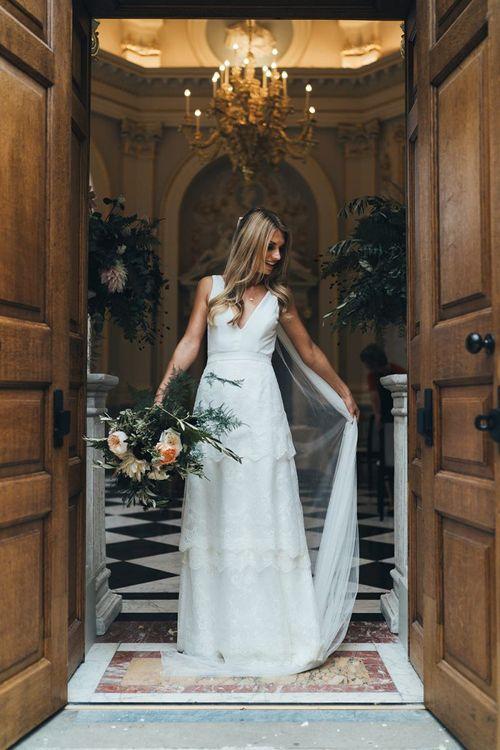 Bride Adjusting Veil in Charlie Brear Tiered Wedding Dress