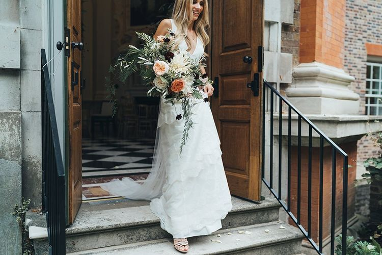 Bride With Relaxed Peachy Wedding Bouquet in Charlier Brear Wedding Dress
