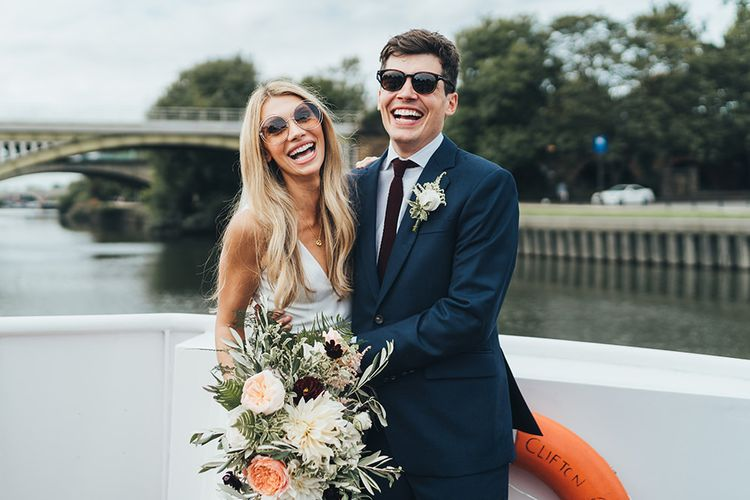 Bride and Groom in Sunglasses in Boat to their Richmond Reception Venue