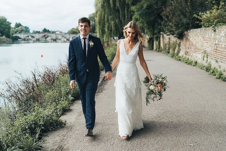Bride & Groom Stroll Next to Thames River in Charlie Brear Dress and Hackett Suit