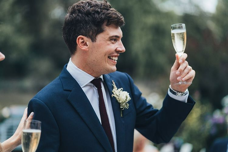 Groom Raising a Toast During Day with Navy Suit and Burgundy Tie