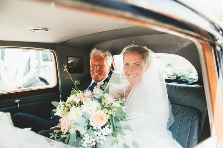 Beautiful Bridal Entrance in Wedding Car Holding White and Peach Bouquet