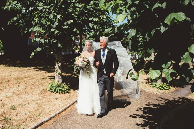 Bride in Tulle and Applique Halfpenny London Wedding Dress and Father of The Groom Walking Through the Church Courtyard