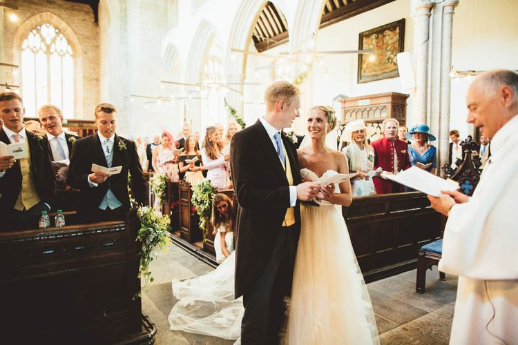 Bride and Groom at the Altar with Bride in Halfpenny London Wedding Dress and Groom in Traditional Morning Suit