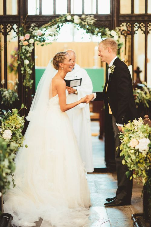 Bride in Tulle and Applique Wedding Dress and Groom in Traditional Morning Suit Exchanging Wedding Vows at the Altar