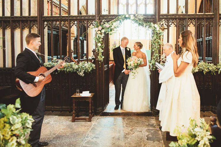 Bride and Groom Standing at the Altar with Church Wedding Flowers