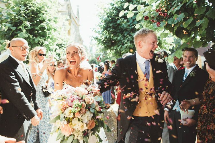 Confetti Moment with Bride in Halfpenny London Wedding Dress Holding a Blush, White and Green Bouquet and Groom in Traditional Morning Suit