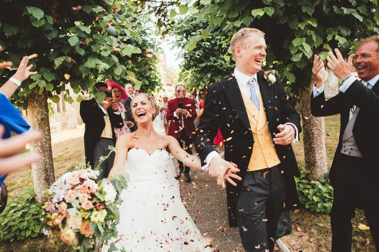 Confetti Exit with Bride in Halfpenny London Wedding Dress Holding a Blush, White and Green Bouquet and Groom in Traditional Morning Suit