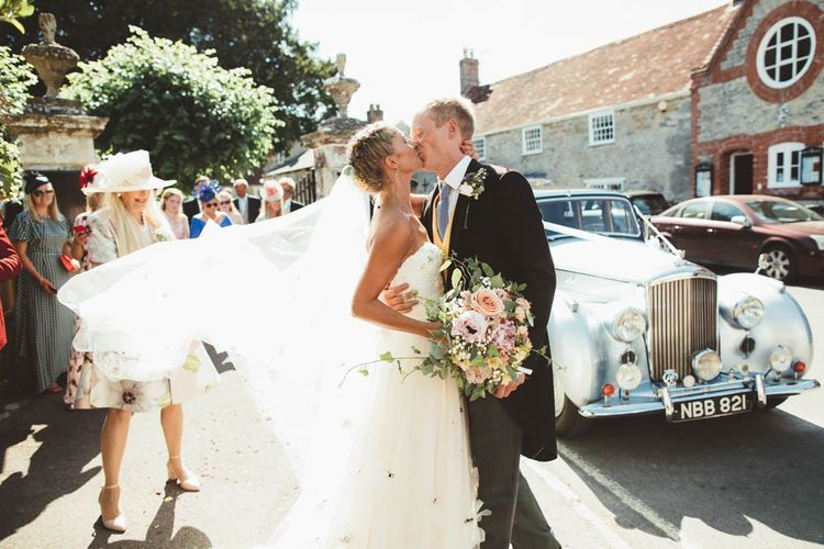 Bride in Halfpenny London Wedding Dress  with Braided Up Do and Groom in Traditional Morning Suit Kissing Next to Their Wedding Car