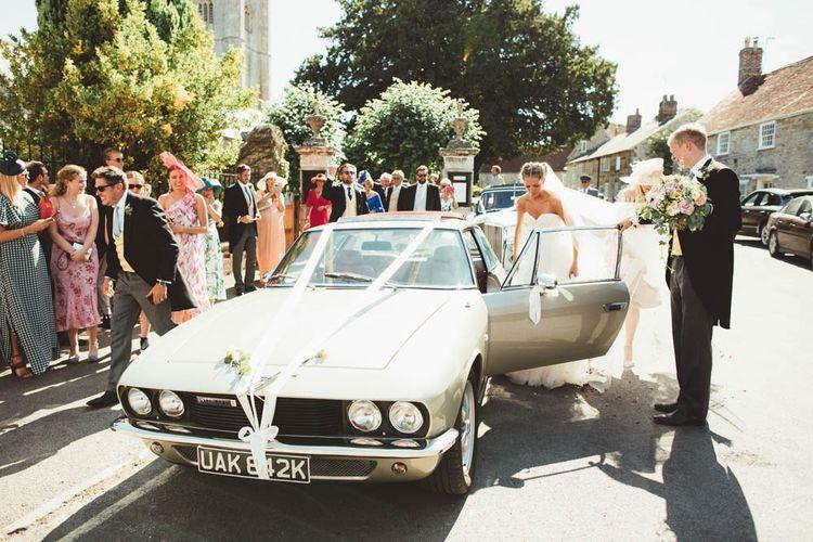 Groom Helping His Bride into their Vintage Wedding Car