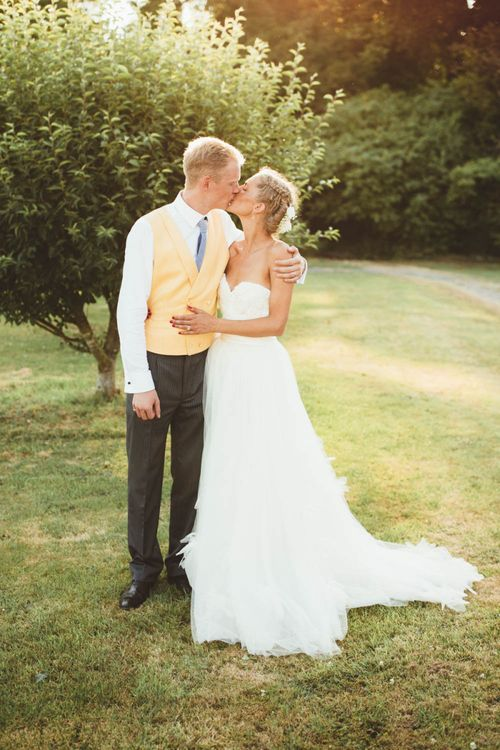 Bride in Tulle and Applique Halfpenny London Wedding Dress with Groom in Yellow Waistcoat and Blue Tie Hugging