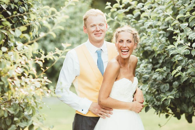 Bride in Tulle and Applique Halfpenny London Wedding Dress with Groom in Yellow Waistcoat and Blue Tie Embracing