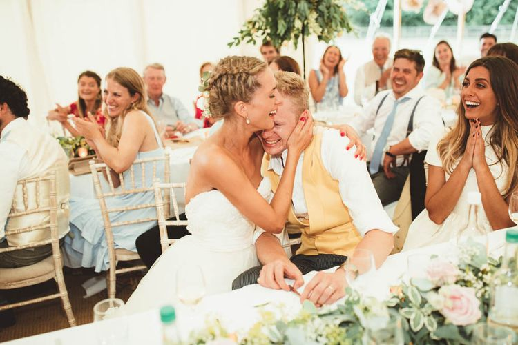 Bride in Tulle and Applique Halfpenny London Wedding Dress with Groom in Yellow Waistcoat Laughing and Joking During Marquee Wedding Reception