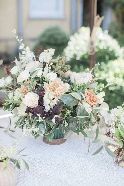 Peach and white flower arrangement with foliage