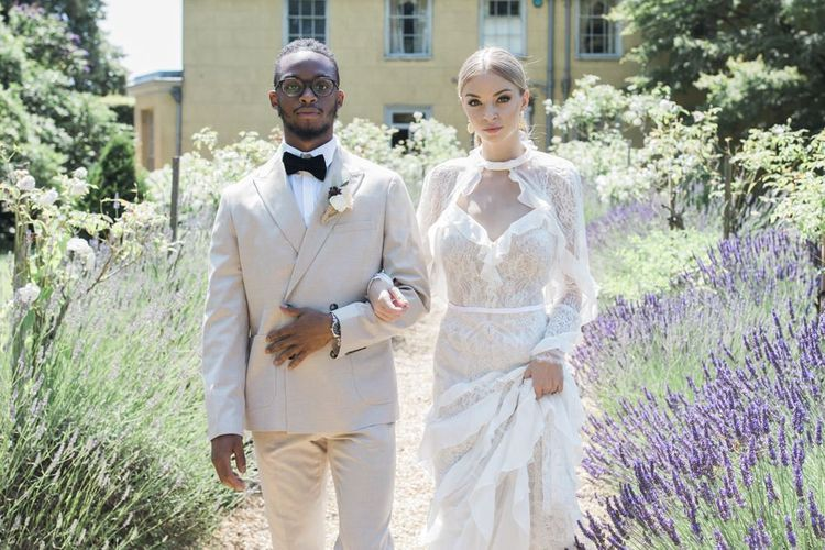 Stylish bride and groom standing amongst the lavender at The Old Rectory Estate