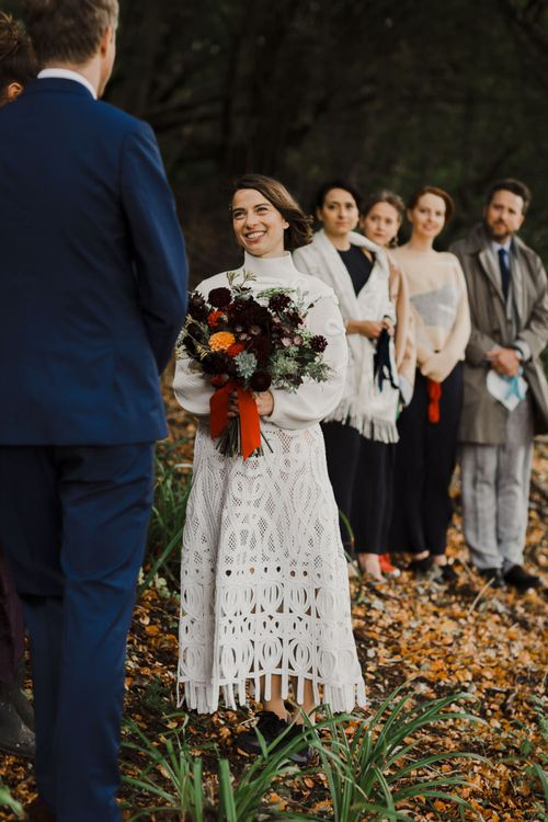 Boho Bride in Crochet Wedding Dress and Woollen Jumper with Red and Orange Dahlia Bridal Bouquet