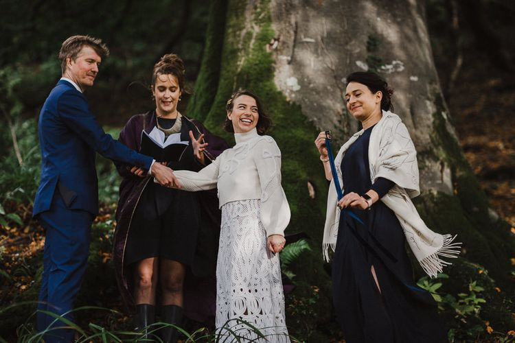 Bride in Crochet Wedding Dress and Woollen Jumper and Groom in Navy Suit During the Wedding Ceremony