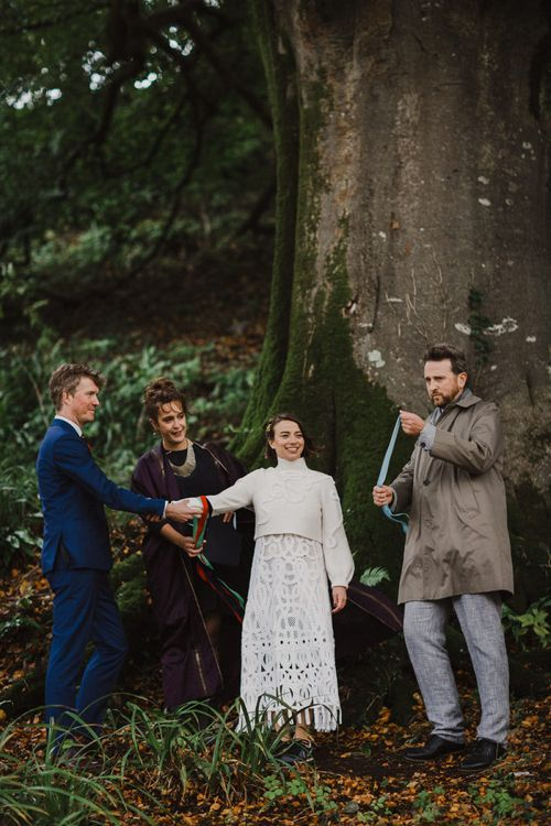 Bride in Crochet Wedding Dress and Woollen Jumper and Groom in Navy Suit Holding Hands During the Wedding Ceremony