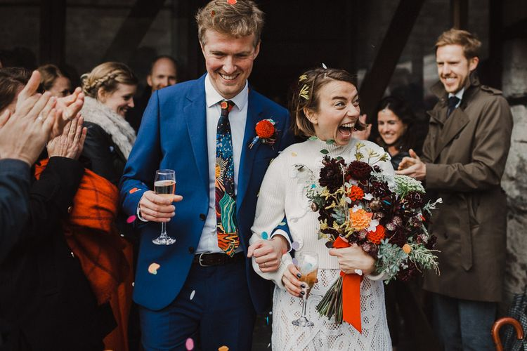 Confetti Moment with Happy Bride in Crochet Wedding Dress and Woollen Jumper and Groom in Navy Suit
